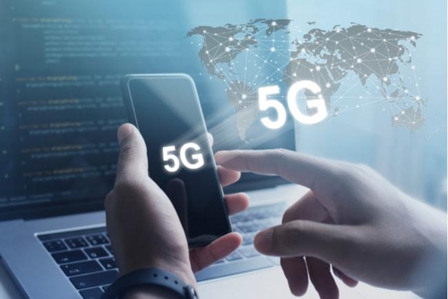 Illustration 5G och jorden. Vänsterhand håller i mobiltelefon och högerhand trycker på pekskärmen, i bakgrunden en laptop