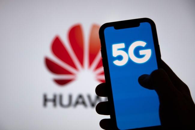 Huaweis logga i bakgrunden och en hand som håller i en mobil med 5G.
