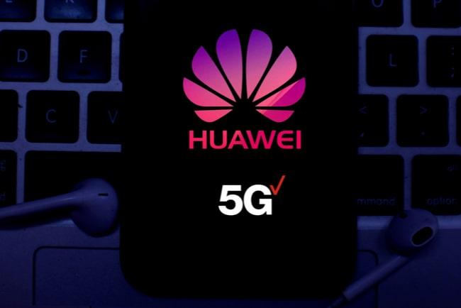 Huaweimobil ligger på ett tangentbord med två hörlurar bredvid.