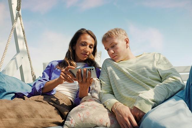 Mamma och son sitter och tittar på film tillsammans i en mobiltelefon.
