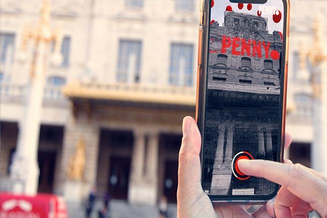 Hand håller upp en mobiltelefon framför Dramaten i Stockholm och tar ett kort.