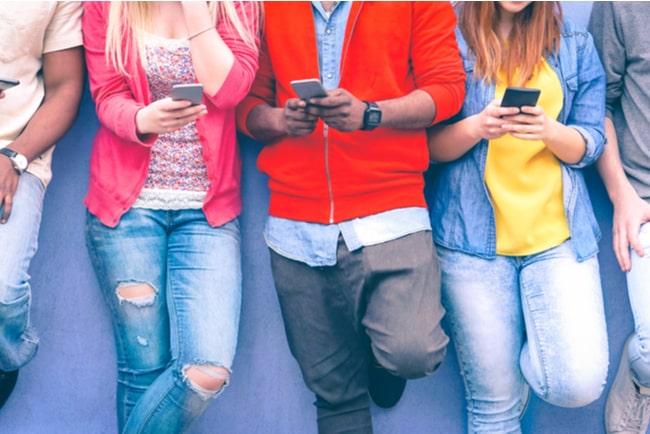Fyra personer står längs en vägg och pillar på sina mobiltelefoner.