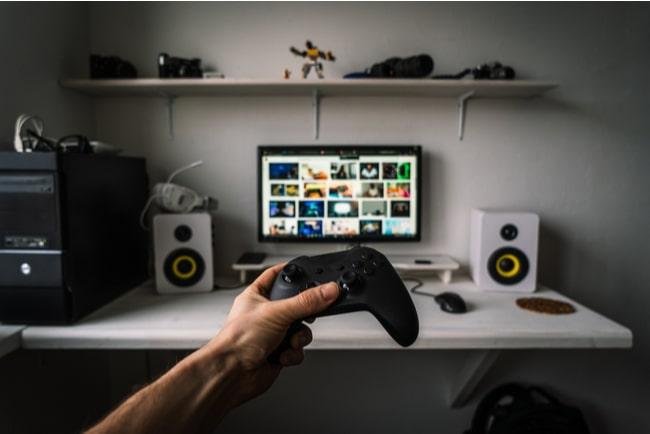 Hand håller upp en xbox handkontroll framför en surfplatta på ett skrivbord