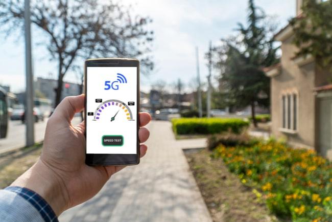 Hand med smartphone mäter hastighet med 5G-uppkoppling på en gata.