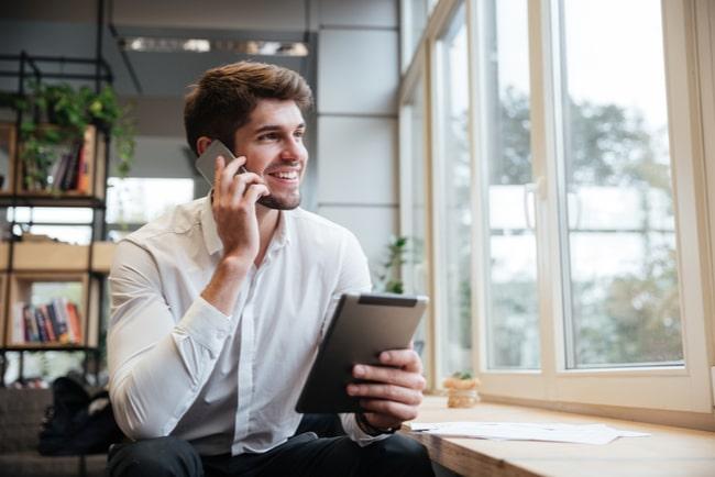 leende man pratar i mobil med surfplatta i handen på café