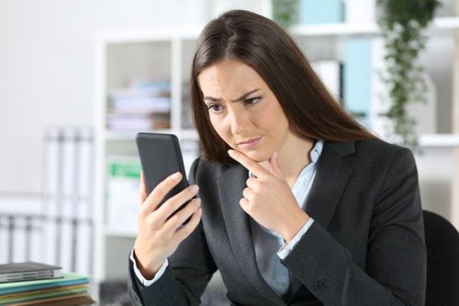 Affärskvinna tittar misstänksamt på smartphone på kontor.