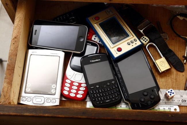 Flera gamla mobilmodeller ligger i en byrålåda.