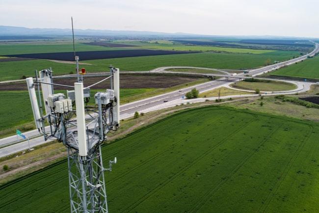 mobilmast med motorväg och gröna fält i bakgrunden