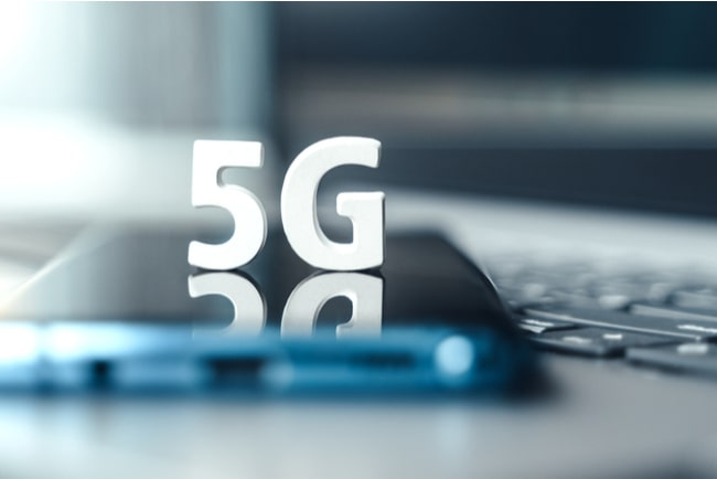 Mobiltelefon ligger på tangentbordet på en laptop med en 5G-symbol ovanpå.