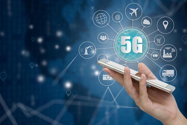 Hand håller i en mobiltelefon med 5G och symboler som visar olika kommunikationsnätverk.