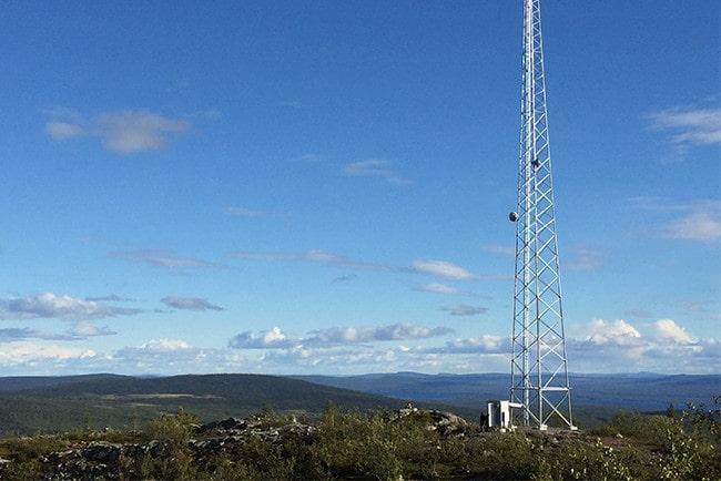 Mobilmast från Tele2 på en höjd i ett öppet landskap med blå himmel