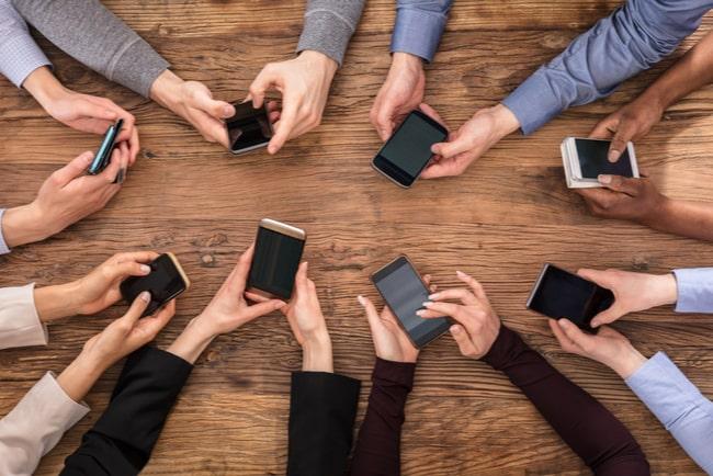 händer med mobiler vid ett bord