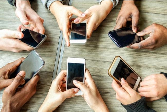 en ring av människors händer som håller i mobiltelefoner