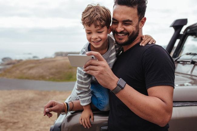 leende far och son tittar på telefonen under bilutflykt till ett naturlandskap