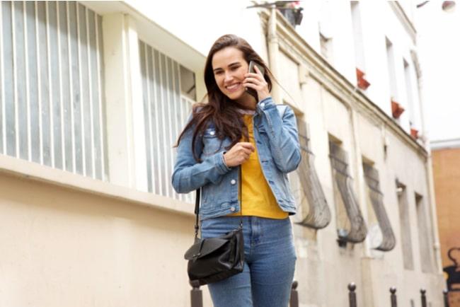 glad kvinna pratar i mobiltelefon i stadsmiljö