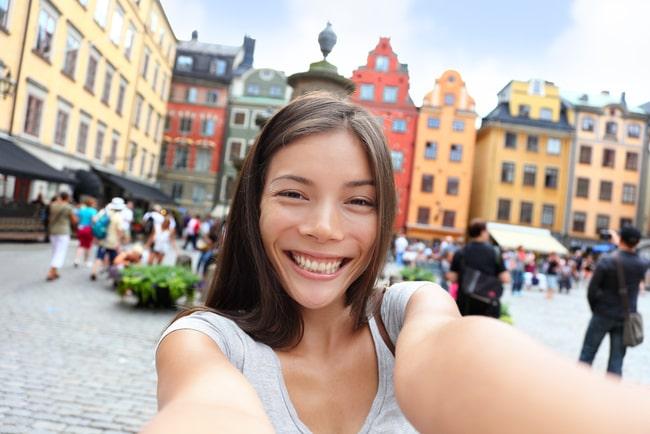 asiatisk kvinna tar selfie i stadsmiljö