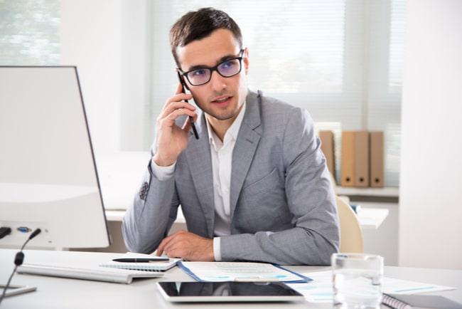Man i grå kostym på jobbet pratar i telefon