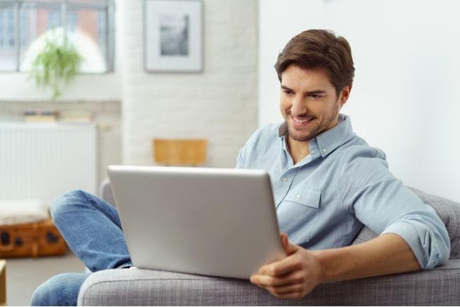 Man sitter i soffa med dator