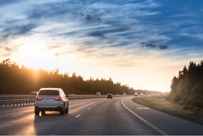 bil på motorväg i solnedgång