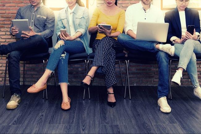 människor som sitter på en bänk med datorer