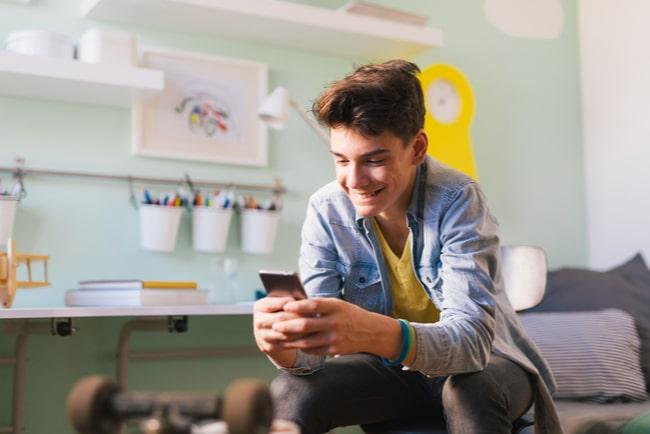 Tonårskille surfar på mobiltelefon