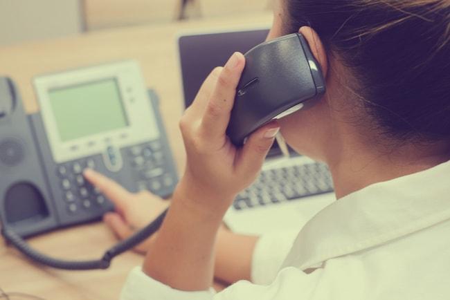 kvinna på kundcenter svarar i växeltelefon