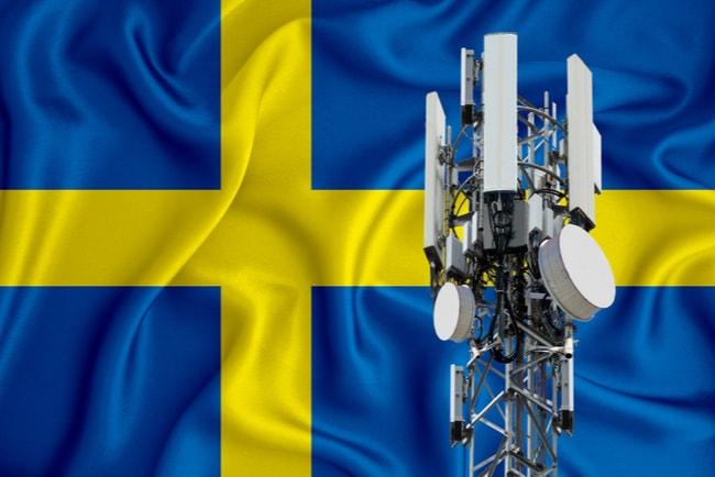 Svenska flaggan i bakgrunden och en 5G mast.
