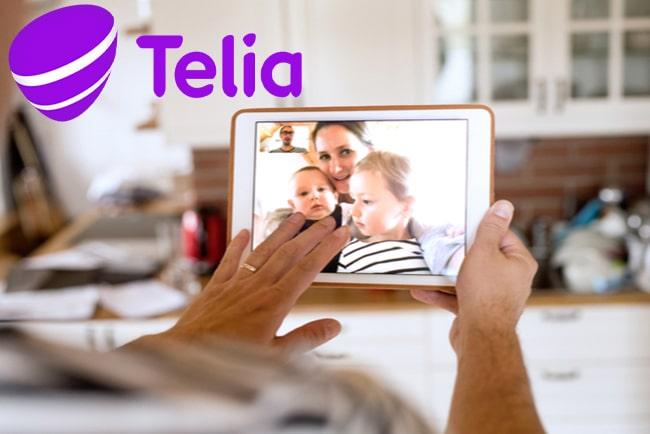 Två händer som håller i en surfplatta och har videosamtal med en kvinna och två barn och Telias logga i vänster hörn.